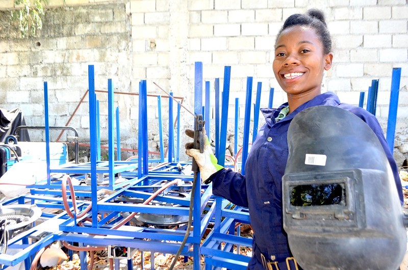 """Vionise Fortuna, 28, lives in Martissant, Haiti. She works for LEAD subgrantee SWITCH to manufacture gas stoves. """"I always dreamed of working in a traditionally male profession,"""" she says. """"I thought, if they can do it, I can do it too. I love making these gas stoves. I'm helping with the preservation of nature."""""""